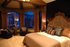 Luxurious master bedroom with purple walls and an ornate headboard.
