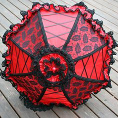 https://flic.kr/p/bRLcii | red parasol black lace 1 | A red satin parasol with alternating panels of lace overlay and ribbon lacing, embellished with almost 19 yards of trim and Venice lace.