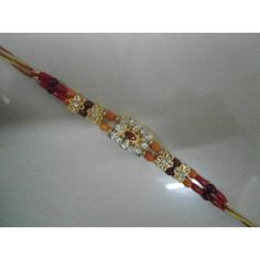 Center design of the rakhi is studded with stones in a floral pattern. Rakhi will surely be appreciated by every one. rakhi is further followed by four golden flowers and beads on the thread.    Free Pack of roli chawal and A bar of chocolate comes along.    Free delivery in India.
