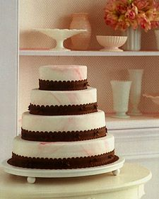 Bakers have been swirling dark and light batters together for more than a hundred years. Here, marbleized fondant hints at the cake's interior and covers a layer of buttercream frosting. The fondant's soft pink hue contrasts with the scalloped chocolate bands, charmingly dressed with grosgrain ribbons and silk bows. Inside are actually two kinds of cake, chocolate marble and mocha marble, in alternating layers; the espresso in the mocha brings extra sophistication to the combination of…