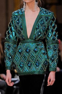 balmain fall 2013 extravagant quilted metallic vinyl jacket with deep V-neck, full sleeves, and highlighted waist. Balmain incorporates quilted fabrics in several collections throughout the years.