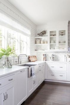 Welcoming white kitchen is fitted with a stainless steel apron sink paired with a modern nickel faucet and fixed between a white quartz countertop complementing white shaker cabinets finished with nickel pulls.