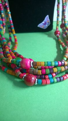 Brightly coloured wooden beaded necklace. The small beads are interspersed with larger beads & silver colour spacers by ThePemburyEmporium on Etsy