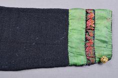 Spedetröja i blåsvart ullgarn garnerad med band och broderier kring halsringning, på bröstet och vid nederdelen på ärmen.  Tröjan är slätstickad med mönsterstickning på axeln, längs nederkanten och på fram- och bakstycke vid ärmens isättning. Litet skört mitt bak. Gröna sidenband (30 mm breda) runt halsringning, på bröstet och nederdelen på ärmen. Bröstet är dekorerat med broderier i rödrosa, vitt och orange i plattsöm, stjälksöm och kråkspark/gles flätsöm ovanpå de gröna banden. Ärmen är…