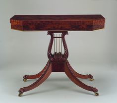 "Card table, unknown artist originally attributed to Duncan Phyfe, 1810-20, p.444 (""A mahogany games table that from where I stood looked like it might be Duncan Phyfe"")"