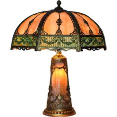This is a large and impressive slag glass lamp with lighted slag glass base.  The shade has an intricately  designed filigree pattern and bi-color