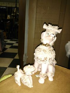Pink porcelain poodle family sport gilt accents and spaghetti style faux fur. These charming 1950's dogs are a cute accent for dresser or vanity. Missing one poodle and the hat is chipped on the mother. Mother-6″H/baby poodles-2.5″H x 2″L   Asking $75.00 with shipping