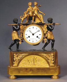 Pendule au nègre, bronze ciselé et doré, patiné représentant Paul et Virginie portés par deux noirs. premier quart du XIXe, 47 x 30.
