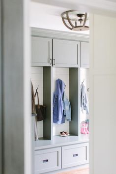 Grey mudroom features gray mudroom cabinets adorned with oil rubbed bronze pulls stacked over open mudroom lockers lined with shiplap.
