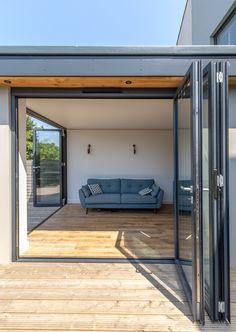Modern bi-fold doors   grey aluminium profile   level threshold   timber decking   timber floor  