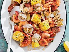 Grilled Clambake Foil Packets with Herb Butter Recipe | Mesh bags are traditionally used at clambakes. For this recipe, however, we have added the classic low country boil ingredients of shrimp, potatoes, corn, and smoked sausage, such as Conecuh. We prefer using foil packets because they act as pockets, catching the seasoned juices and buttery sauce—perfect when used as a dipping sauce with a hunk of bread. You can quickly assemble the foil packets in the morning and store them in the…
