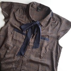 Ann Taylor Silky Dress Shirt Feminine and professional! This top is perfect to pair with a blazer or pencil skirt. Features short fluttery sleeves, two front pockets, and a front tie. Ann Taylor Tops Blouses