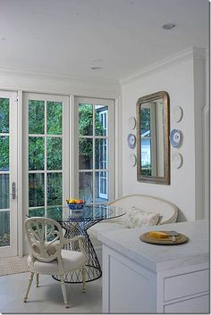 Breakfast Nook - French settee with a pillow paired with a contemporary wire table and arm chair.