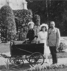 Czar Nicholas II with his 2 youngest children, Czarevich Alexei and Grand Duchess Anastasia. That looks like Joy the Spaniel in the cart with Alexei.