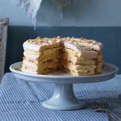 almond flour meringue cake has layers of silken pineapple french buttercream, caramelized pineapple, and crisp praline