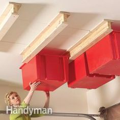 Hang storage bins from the ceiling by making your own support carriages and buying plastic totes.  Perfect for holiday decor!