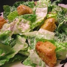 Ceasar Salad Dressing  6 cloves garlic, peeled     3/4 cup mayonnaise     5 anchovy fillets, minced     6 tablespoons grated Parmesan cheese, divided     1 teaspoon Worcestershire sauce     1 teaspoon Dijon mustard     1 tablespoon lemon juice     salt to taste     ground black pepper to taste     1/4 cup olive oil     4 cups day-old bread, cubed 1 head romaine lettuce, torn into bite-size pieces