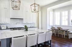 Amazing kitchen features a pair of Small Darlana Lanterns in Hand Rubbed Antique Brass illuminating a gray kitchen island topped by by white marble countertops lined with four light gray linen counter stools.