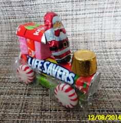 Lifesaver Christmas candy train. One roll lifesavers, 1 pack Doublemint gum, 4 starlight mints, 3 Starbursts, 1 Rolo, 1 Hershey's mini chocolate bar, 1 chocolate Santa, hot glue together.