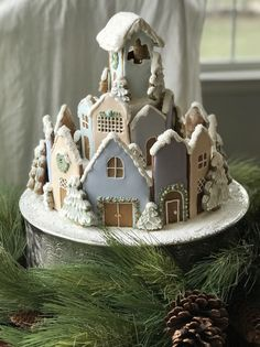 Gingerbread Christmas village with pastel houses and flocked snowy trees. DIY gingerbread house! Decorated cookies #gingerbreadrecipeeasy