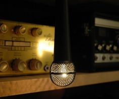 The Modern Solo Light was designed by Donna Brady and features a cherry wood veneer body completed with a gold colored metal mesh globe allowing the 6 watt indicator light bulb to shine through.