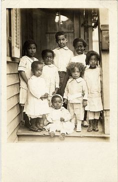 8 unidentified American American children posing on porch.