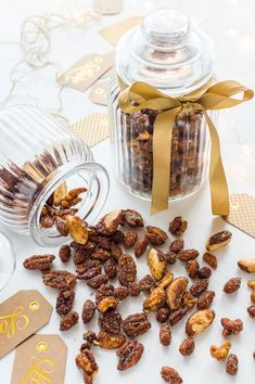Spiced honey roasted mixed nuts tumbling out of a glass cookie jar with ribbon and gift tags.