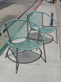 This pair of hoop chairs is such a classic example of mid-century seating for an outdoor patio space. They were recently redone with new vinyl straps in blue moss and powder coated frame in lava. The straps have both blue and green present, so it would really complement either patio