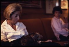 Middle-aged woman and her Yorkshire terrier seated on a sofa, a boy looks on, 1972
