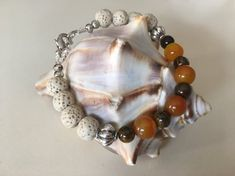 This uniquely handcrafted adjustable bracelet from Simply Charmed Jewelry has a nice mixture of warmth with the orange moonstone and tigers eye beads. The beige lava beads blend in nicely. The properties of these two gemstones work nicely together. The orange moonstone is the perfect stone for women Handmade Bracelets, Handcrafted Jewelry, True Gift, Lava Bracelet, Tiger Eye Beads, Sparkly Jewelry, Healing Bracelets, Adjustable Bracelet, Jewelry Making