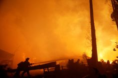 Firefighters try to stop a fire as the worst wildfires in Chile's modern history ravage wide swaths of the country's central-south regions
