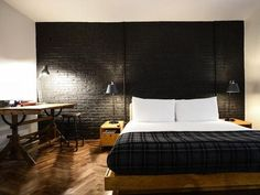 This Ace Hotel bedroom is cozy, yet uncluttered. The black wall behind the platform bed adds a subtle, stark interest to the space, and the task lighting makes everything feel utilitarian. Black Brick Wall, Black Walls, Black Accent Walls, Red Walls, Teen Bedroom, Bedroom Decor, Bedroom Ideas, Bedroom Pictures, Bedroom Black