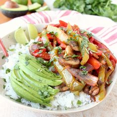 Sautéed, seasoned veggies are served on top of cilantro lime rice with fresh avocado for a flavorful, easy to make, vegan and gluten free fajita recipe!