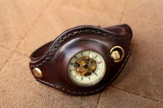 Pocket watch in custom leather wrist strap. Follow the link to get some clues as to how it's made.