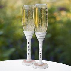"Rustic Love Toasting Flute Set includes two toasting flutes. The base and stem are made of resin carved and painted to look like birch wood. The top of the base is painted to look like exposed wood. Each stem is carved with the word ""LOVE"" in black. Sitting atop each stem is a clear glass bowl in a classic flute shape."
