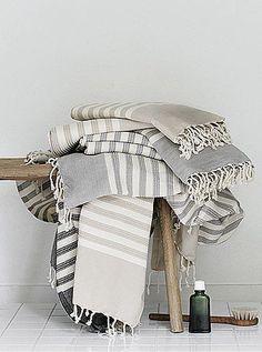 neutral bathroom bathroom accessories + turkish bath towels   rustic wood stool
