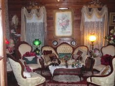 Iconic Victorian except for the walls. A strange juxtaposition of such fancy furniture and fixings. I love the lacy curtains, the table runner, and the oriental rug - all typical of downhome Victorian.