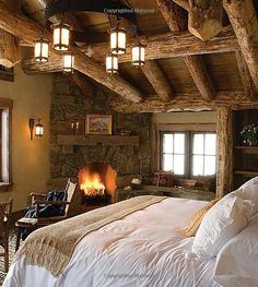 Rustic Elegance in this Mountain Cabin Master Bedroom with cozy fireplace. I like the contrast of the rustic architecture against the elegant bedding. From the book, Rustic Elegance