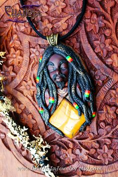 Rastaman Rasta Love piece by ChaNoJaJewelry. Rastafari Jahbless, Rasta Jewelry. This Rasta Man is something a little different. He represents strength and Love. It was so much fun to create another Rasta Man with beard! He is really unique, nowhere else to be found. In this piece I combined a wonderful square tigers eye gemstone and a tribal triangle. I incorporated the Rasta Colors Red Gold Green and I just loved to make the tiny rasta dreadlock beads he wears!