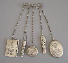 Chatelaine, contains the notebook, a pocket knife, perfume holder, pocket mirror, a photo locket, and powder.