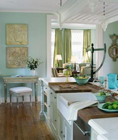 airy, pretty kitchen    integrated with the room--love the curtains with the turquoise walls.