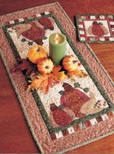 "Enjoy the Pumpkin Patch Set digital pattern from Love of Quilting September October 2011 issue. Make the matching set for your autumn table. Machine applique using fusible web and blanket stitch, and get it done in no time!  Quilt designed by Kelly Mueller. Table runner size is 33 1/2"" x 16 1/2"". Hot Pad Size is 8 1/2"" x 8 1/2"". Digital pattern only $5."