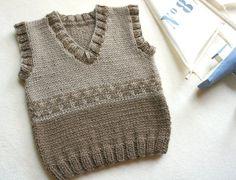 Beige and brovn Hand knitted toddler vest. Made from soft and light weight Baby Yarn 100%wool. This vest could be a great for layering in winter or just over a T-shirt on summer evenings. Measures: 13 long (33 cm), Finished Chest: 21 (56 cm) size 2y Washing machine on gentle in cool