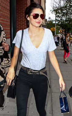 Kendall Jenner played up a simple gray tee and high-rise black jeans with oversized aviators flaunting red flash lenses and a studded belt!