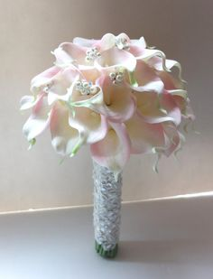 This Beautiful blush pink calla lily bouquet is just elegant for its simplicity. Accented with pearls & crystals and finished with beautiful textured lace.  Measures are around 9 x 12 inch. approx 40 calla lilies Let us know if you prefer a ribbon and brooch handle instead of lace.  Want a calla lily bouquet without pearls ? https://www.etsy.com/listing/94998248/blush-pink-calla-lily-bouquet-bridal?ref=shop_home_active_1  Door to door lead time around 4 weeks...