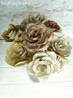 DIY Book Page Flowers. This is such an elegant and simple home decor project. Would also make a nice centerpiece for a rustic wedding or spring party or shower. Click through for the full tutorial for this easy DIY project.