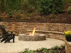 Stone wall cut into the hill with round stone fire pit.