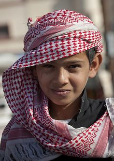 Flower men tribe kid, Saudi Arabia. Photographer's Description: The flower men live in Yemen and Saudi Arabia. They wear a headdress made with fresh flowers and grasses. They still live in a very tribal way, and do not like to meet foreigners. Meeting them in the souq of Al Farsha is a special time as you need a police escort and a lot of diplomacy to go in the area. (Evidently the kids don't wear the headdress of flowers) (V)