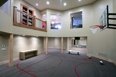 Michigan home for basketball lovers. This carpeted indoor basketball court can be seen from all of the main rooms in the house, so the family members can cheer one another on. Houzz users loved how this incredible court can double as a workout room. Home Basketball Court, Basketball Room, Sports Court, Basketball Shoes, Louisville Basketball, Basketball Legends, Basketball Uniforms, Basketball Camps, Basketball Finals