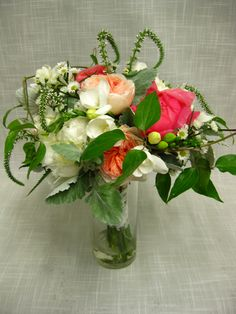 Handtied bridal bouquet of coral and cream garden flowers including peonies, Juliet garden roses, veronica, freesia, asters and clematis vine.